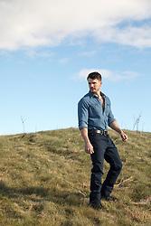 man walking on a grassy hillside