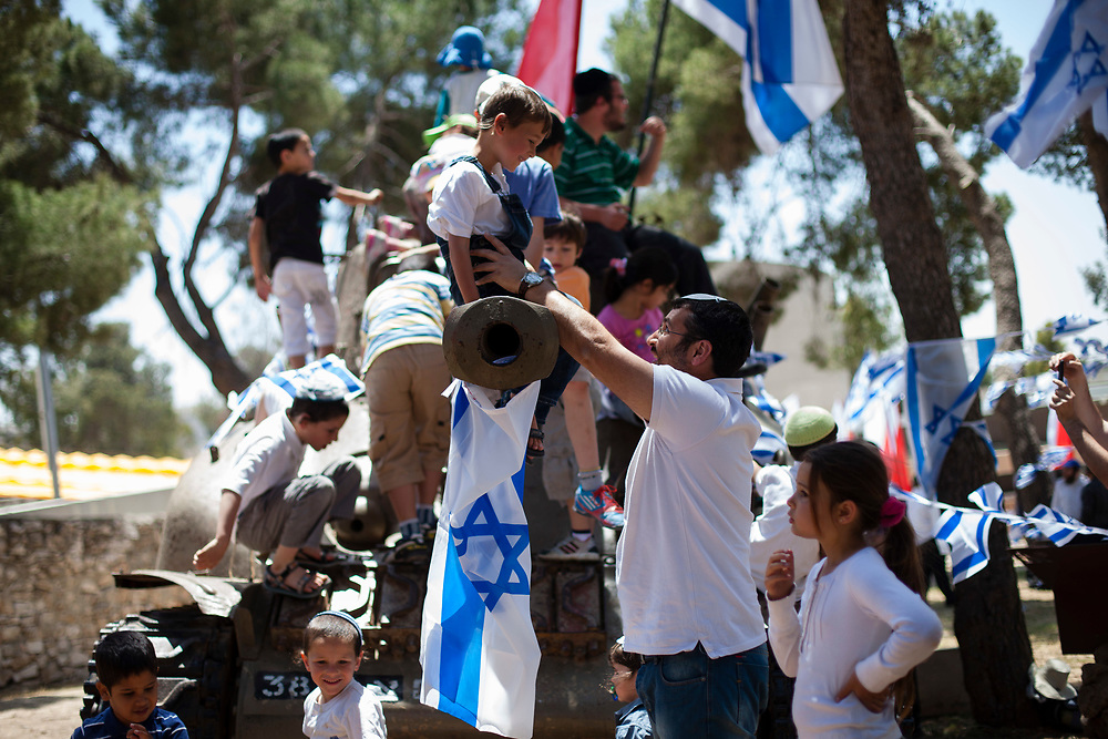 Israeli children play on top of an old military tank decorated with Israeli flags as part of Israel's 64th Independence Day anniversary celebrations, at the Ammunition Hill national memorial site in Jerusalem, Israel, on April 26, 2012.