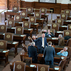 Republican Texas House members mill about the chamber on the second day of failing to get a quorum at a special session. Most Democratic members left the state protesting of restrictive voting measures proposed byTexas Gov. Greg Abbott.