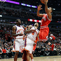12 March 2012: Chicago Bulls point guard Derrick Rose (1) goes for the layup over New York Knicks center Tyson Chandler (6) and New York Knicks power forward Amare Stoudemire (1) during the first half of New York Knicks vs Chicago Bulls, at the United Center, Chicago, Illinois, USA.