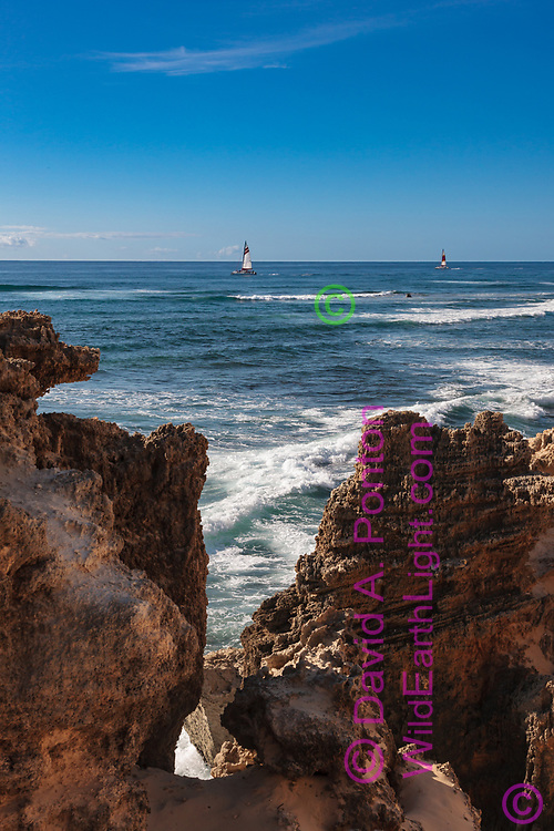 Sailboats cruise along rugged coastal formations on the southeastern shore of Kauai, © David A. Ponton