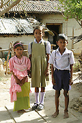 IND.MWdrv04.423.x..Seema Yadav, in pink, and her sister and brother?Aarti and Anurag (called Guddu) are dressed and ready for school in Ahraura Village, Uttar Pradesh, India. Revisit with the family, 2004. The Yadavs were India's participants in Material World: A Global Family Portrait, 1994 (pages: 64-65), for which they took all of their possessions out of their house for a family-and-possessions-portrait. Child, Children, Education..