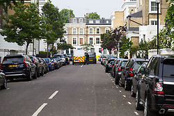 A police van, a private ambulance and a forensics tent in Cathcart Road, Chelsea, mark the scene of yet another London murder following the fatal stabbing on the night of May 30th 2018 of a man in his forties, said to be a delivery driver who refused to hand over his cash to robbers. London, May 31 2018.