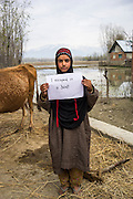 """Apsa Darifa, 10, holds up a sign with the message """" I escaped in a boat"""", next to her house which was flooded in September in Purnishadashah village, Jammu and Kashmir, India, on 24th March 2015. Apsa had to flee her house in a boat when the floods came. She had no time to take any of her belongings. Save the Children supported her with an education kit to replace the school books she had lost. Photo by Suzanne Lee for Save the Children"""