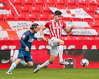 Stoke City's Danny Batth brings the ball forward under pressure from Derby County's Patrick Roberts<br /> <br /> Photographer Lee Parker/CameraSport<br /> <br /> The EFL Sky Bet Championship - Stoke City v Derby County - Saturday 20th March 2021 - bet365 Stadium - Stoke-on-Trent<br /> <br /> World Copyright © 2021 CameraSport. All rights reserved. 43 Linden Ave. Countesthorpe. Leicester. England. LE8 5PG - Tel: +44 (0) 116 277 4147 - admin@camerasport.com - www.camerasport.com