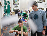 SUNY Sullivan student Chris Sherwin of Walden, at left, hooks up wires from a model windmill to a battery at the Eco-Fair at DeHoyos Gallery on the campus in Loch Sheldrake as assistant professor of wind turbine technology Larry Reeger watches on Wednesday, Oct. 24, 2012.  The college's S.E.E.D.S. (Sustainable Energy & Ecological Design Society) club provided information on campus sustainability, and raising funds through the sales of water bottles, meal kits, and raffle tickets at the Eco-Fair, which was part of Campus Sustainability Day.