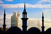 Typical of the British Raj architectural style, spires of the old Kuala Lumpur Railway Station (foreground) frame the soaring skyscrapers of a modern Islamic state in Kuala Lumpur, capital of Malaysia. British colonial architects favored the domes, arches, and airy interiors typical of Muslim India and the Middle East. But today's sleek office towers of glass, steel, and concrete put a premium on function over form  a trend that has transformed the skylines of Asian cities. © Steve Raymer / 2002 ALL RIGHTS RESERVED