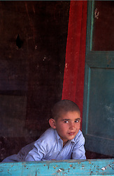 MAKHFI SCHOOL, 30 July 2005..Boy behind the mosquito net.....Most of the 'one room' school are located in private houses. The VTC aim is to make women aware of  their onwn status as Mother and as Woman, by  giving lessons on maternity, health, family planning and post-natal issues. ..According to United Nations Population Fund, Afghanistan has among the world?s highest rates of maternal mortality, and Badakhshan has the highest rates ever recorded anywhere in the world, with one mother dying in every 15 births. ..Underage marriage is one of the primary causes of maternal mortality.....The VTC is funded by UNFPA and implemented by IBNSINA.