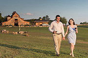 A young couple walks hand-in-hand at a winery.