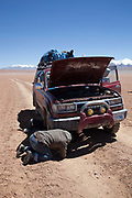 Bolivian man fixing a 4 x 4 in the desert. Salar Uyuni salt flats and Eduardo Avaroa national park, south western Bolivia