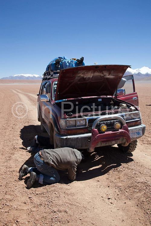 Bolivian man fixing a 4 x 4 in the desert. Salar Uyuni salt flats and Eduardo Avaroa national park, south western Bolivia