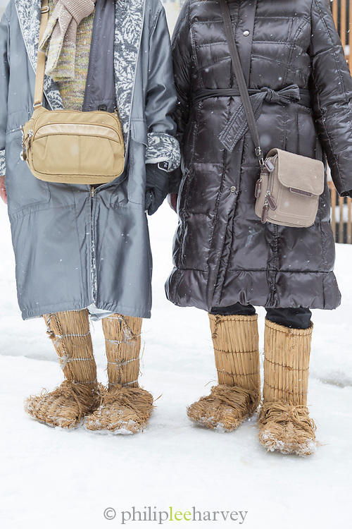 Two women wearing boots made of straw, Nozawaonsen, Japan