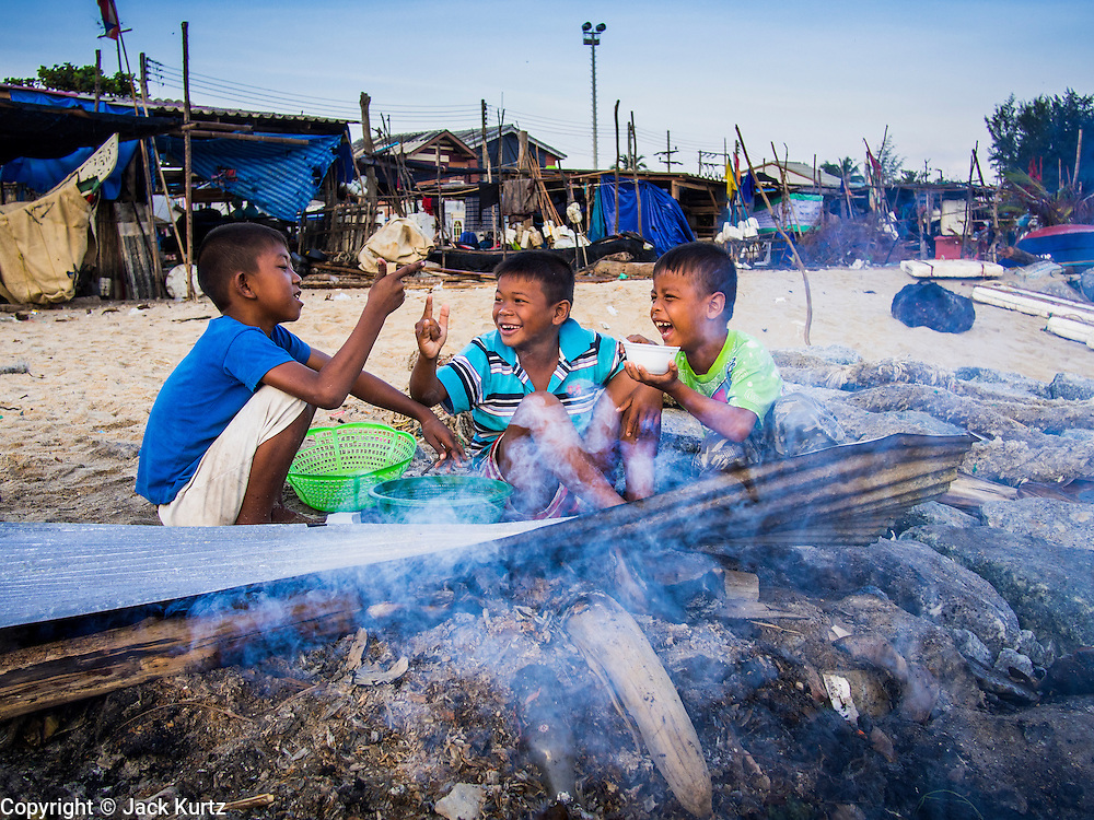 07 FEBRUARY 2014 - KAO SENG, SONGKHLA, THAILAND:  Children whose fathers own small fishing boats play around a cooking fire in Kao Seng. Kao Seng is a traditional Muslim fishing village on the Gulf of Siam near the town of Songkhla, in the province of Songkhla. In general, their boats go about 4AM and come back in about 9AM. Sometimes the small boats are kept in port because of heavy seas or bad storms.     PHOTO BY JACK KURTZ