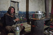 Yondchen Zema, a Tibetan nomad in the village of Sumdho on Ladakh's Changtang plateau, knits while preparing tea.