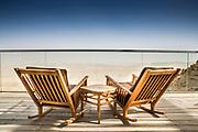 Deckchairs on a wooden deck overlooking a vast barren landscape. Photographed at the Ramon Creater, Negev Desert, Israel