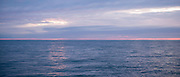 Breathtaking, spectacular pastel colours of setting sun above the calm sea of the Atlantic Ocean in Wales