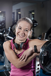 Mid adult woman taking a break after exercising and smiling in the gym, Bavaria, Germany