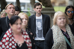 © Licensed to London News Pictures . 30/06/2017 . Stockport , UK . A mourner wearing a Deirdre Barlow prison t-shirt arrives . The funeral of Martyn Hett at Stockport Town Hall . Martyn Hett was 29 years old when he was one of 22 people killed on 22 May 2017 in a murderous terrorist bombing committed by Salman Abedi, after an Ariana Grande concert at the Manchester Arena . Photo credit : Joel Goodman/LNP