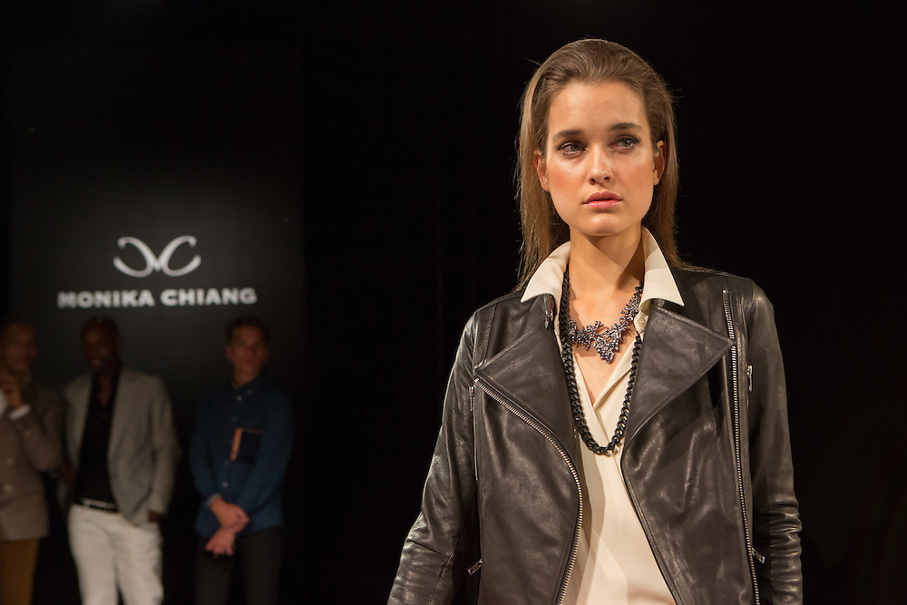A black leather jacket with diagonal zipper which opens to wide lapels over an off-white wrap blouse. By Monika Chiang at Spring 2013 Fashion Week in New York.