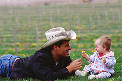 cowboy giving a baby a flower