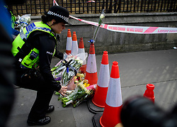 © Licensed to London News Pictures. 23/03/2017. London, UK. A female Police officer lays flowers on Westminster Bridge, the day after a lone terrorist killed 4 people and injured several more, in an attack using a car and a knife. The attacker managed to gain entry to the grounds of the Houses of Parliament, killing one police officer. Photo credit: Ben Cawthra/LNP
