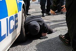 © Licensed to London News Pictures; 04/06/2021; Bristol, UK. A woman lies on the ground after being removed but not arrested by police as police mount a major operation to enter the former Salvation Army building on Dean Lane in Bedminster which has been squatted and arrested 3 people suspected of criminal activity connected with the squatted occupation of buildings in High Street in Bristol city centre which was repossessed earlier this morning by Bailiffs accompanied by around 100 police, but those occupying the buildings in High Street had already left. Those arrested at the Salvation Army building are a 40-year-old man on suspicion of assaulting an emergency worker and escaping lawful custody, a 26-year-old man on suspicion of assaulting an emergency worker and escaping lawful custody, and a woman on suspicion of affray. Police were not evicting the Salvation Army building on Dean Lane as they do not have powers to do so. Photo credit: Simon Chapman/LNP.