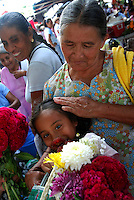 """MEXICO, Veracruz, Tantoyuca, Oct 27- Nov 4, 2009. A young girl and her grandmother shopping for flowers in Santa Maria de Ixcatepec. """"Xantolo,"""" the Nahuatl word for """"Santos,"""" or holy, marks a week-long period during which the whole Huasteca region of northern Veracruz state prepares for """"Dia de los Muertos,"""" the Day of the Dead. For children on the nights of October 31st and adults on November 1st, there is costumed dancing in the streets, and a carnival atmosphere, while Mexican families also honor the yearly return of the souls of their relatives at home and in the graveyards, with flower-bedecked altars and the foods their loved ones preferred in life. Photographs for HOY by Jay Dunn."""