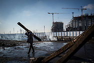 Migrant carring a railway wood sleepers that will be used for bonfire inside the warehouses in an old train deposit in Belgrade, Serbia. 15th January 2017. Federico Scoppa