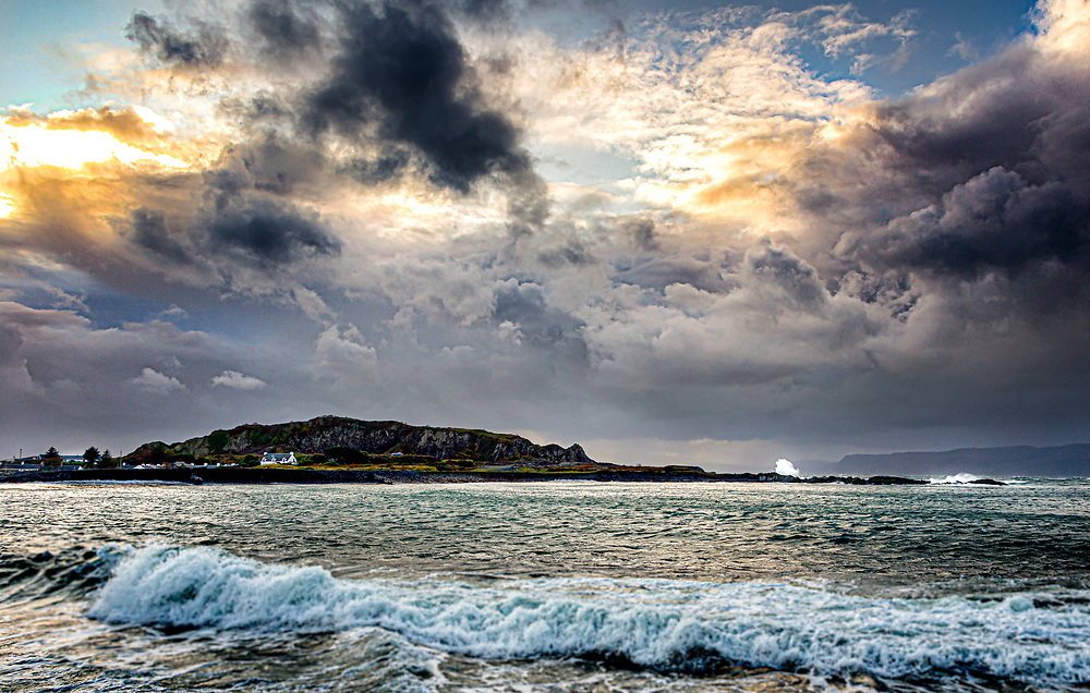 Broken clouds and sun light up the sky above surf and the slate hills of Easdale.