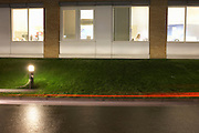 The last person to leave the office is a conscientious lady employee of the biscuit and snack manufacturer United Biscuits at their UK headquarters at Hayes Park North near London England. Seen in a window surrounded bright ceiling lights, the female sits at her desk tying up loose ends before leaving for the day. As darkness falls outside, the red lights from tail lights streak across the picture and the green grass on a landscaped bank is lit by light posts. None of her work colleages have stayed on, preferring to depart to see their families at home on this winter night. Perhaps this career woman is single and an ambitious member of the team who can dedicate more time to her job..