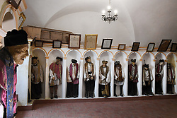 """NO WEB FOR FRANCE - At the crypt of the Mother Church dedicated to San Nicolò of Bari in Gangi, Sicily, Italy on January 2019 one can discover standing well aligned in niches, the well conserved mummies of 44 priests of the parish """"Once a month"""", Father Don Giuseppe known as Pinot said, """"I celebrate the mass here surrounded by my faithful and by my fellows. They remind us that we are passing through this earth and they are still part of our lives years after their departure. You will notice that each one of them displays above their heads a eulogy in the form of a poem retracing their lives.""""<br /> Sicily will reveal over time a real research laboratory on mummification. It is spreading throughout the island and there is not an important village in sight that does not display the bodies of their priests, monks or citizens in the crypt of their church. Photo by Eric Vandeville/ABACAPRESS.COM"""