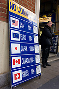 Foreign currency exchange board advertising No Commission in central London. On the board that is propped up against a wall in this busy tourist area, formerly a market of fruit and flowers produce, we see five nationalities' currencies represented with their current rates against the Pound sterling. The US and Canadian Dollar, the Euro, Yen and the Swiss Franc are there with respective flags to attract those wishing to change money.