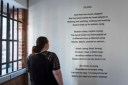 "© Licensed to London News Pictures. 13/11/2018. LONDON, UK. A staff member views poetry by Christina Reihill.  Preview of ""Glad I Did It"", a new work by Irish artist Christina Reihill at Bermondsey Project Space.  The interactive artwork looks at the life and death of Ruth Ellis, the last woman to be hanged in Britain, after she shot her lover, racing driver, David Blakely in 1955.  On display are the artist's interpretation of Ruth Ellis' prison cell, including furniture and props, the hanging room together with a video display of the artist in conversation.   The show runs 14 November to 1 December 2018.  Photo credit: Stephen Chung/LNP"