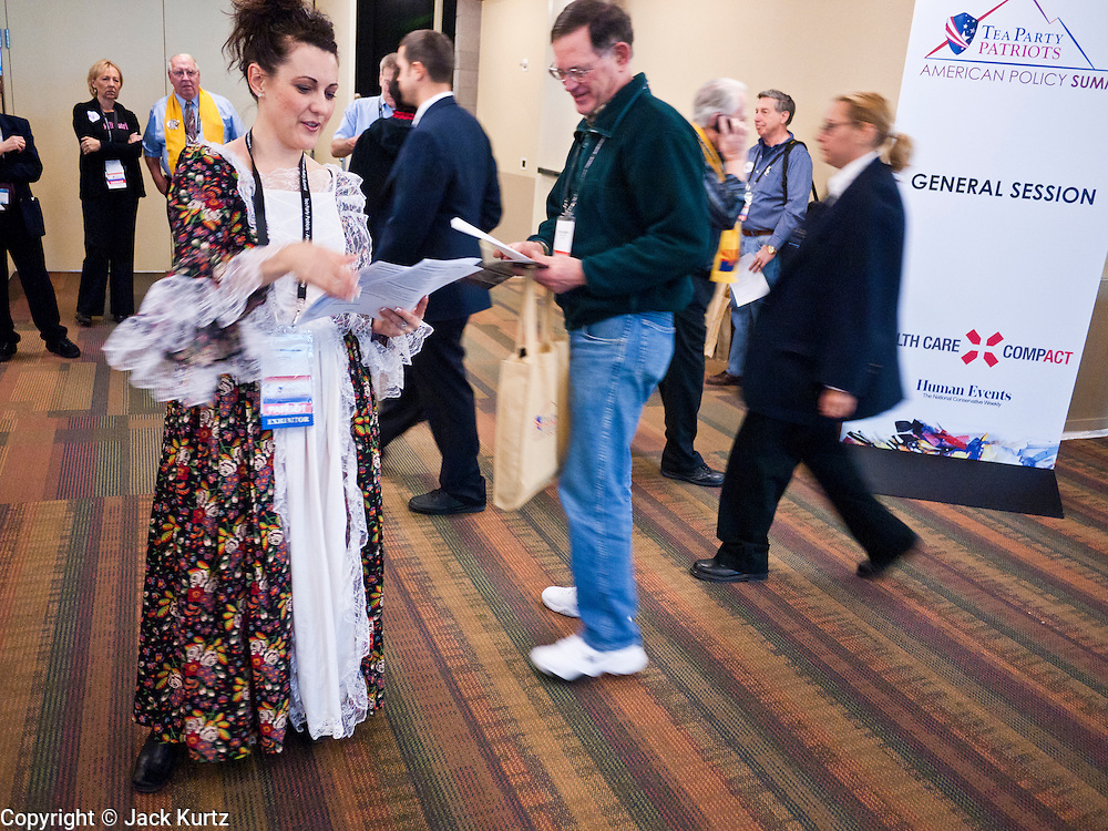 26 FEBRUARY 2011 - PHOENIX, AZ: REBECCA KELSEY, from Gilbert, AZ, hands out schedules to attendees at the Tea Party Patriots American Policy Summit in Phoenix Saturday. The Tea Party Patriots American Policy Summit goes through Sunday Feb. 27. About 2,000 people are attending the event, which organizers said is meant to unite Tea Party groups across the country. Speakers include former Minnesota Governor Tim Pawlenty, Texas Congressman Ron Paul, former Clinton advisor Dick Morris and conservative blogger Andrew Brietbart. The event ends with a presidential straw poll Sunday.   Photo by Jack Kurtz