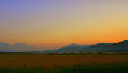 Sunrise over the pasture lands of Jackson Hole creating a golden glow to the east set against the silhouette of the Tetons and the purple twilight receding to the West.