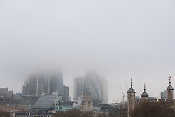 © Licensed to London News Pictures. 17/12/2017. London, UK. London skyscrapers are shrouded in freezing fog this morning. The capital experienced another very cold night with freezing weather. Photo credit: Vickie Flores/LNP
