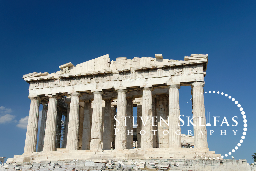 Acropolis. Athens. Greece. View of west (rear) facade of the world famous icon and landmark of Athens the Parthenon Temple which crowns the Acropolis summit. The Parthenon, a temple dedicated to the goddess Athena (Athena Parthenos), was constructed and decorated between 447 and 432 BC. The Parthenon is a Doric style peristyle temple with 17 fluted columns along each side and eight at the ends, which lean slightly inward and bulge out in the centre to cunningly offset the natural optical distortion. The entire Temple, apart from the roof,  were of white Pentelic marble with the sculptures that once decorated the pediments, friezes and metopes all being painted in vivid colours. The Parthenon was the centrepiece and jewel of the monumental rebuilding and transformation of the Acropolis during the time of Perikles. The Acropolis of Athens and its monuments are a UNESCO World Heritage Site.