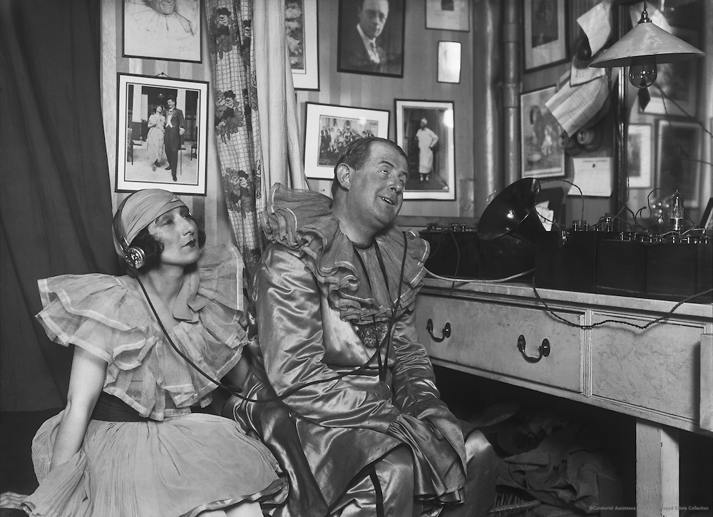 """Betty Chester and Davy Burnaby, stars of the variety show """"The Co-Optimists,"""" listen to an early wireless set with headphones, 1923"""