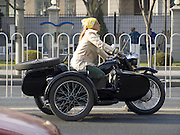 western female on an old Chinese BMW style motorcycle with sidecar