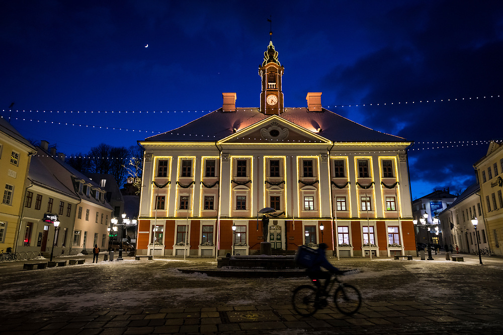 Tartu, Estonia - February 27, 2020: A crescent moon hangs above the town hall on a cold winter night at Raekoja plats (Town Hall Square) in Tartu, Estonia.