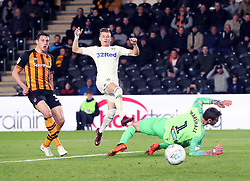 Leeds United's Ezgjan Alioski takes a shot with Hull City's Tommy Elphick (left) and Hull City's keeper David Marshall (right) during the Sky Bet Championship match at the KC Stadium, Hull.