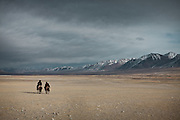 Mustafa Qul and Er Ali Boi, two respected Kyrgyz leader, riding their horses across the Pamir plateau..From Ech Keli to Kyzyl Qorum..Trekking with yak caravan through the Little Pamir where the Afghan Kyrgyz community live all year, on the borders of China, Tajikistan and Pakistan.