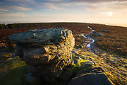 An elevated viewpoint of one of the Ox Stones on Burbage Moor in the Peak District. The glistening path, lit by the dawn sun, leads to the trig point. A sun dog can be seen in the right hand edge of the sky. Derbyshire - South Yorkshire, England, UK. Winter.