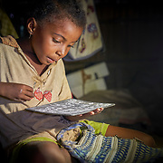 """The grand-daughter of Yollande Randrianambinina sttudies in front of a solar lamp. Dubbed the """"Solar Mamas,"""" Randrianambinina and her friends were the first in their village to join a program by the World Wildlife Fund (WWF) to become electric engineers capable of installing and repairing solar panels. <br /> Across much of this African nation, where 77% of the population of 21 million has no access to electricity -- a figure rising to a staggering 94% among the rural population  -- nighttime means the burning of kerosene lamps and diesel engines, which fill the houses with toxic smoke. And it means the destruction of forests for firewood in one of the world's most biologically-diverse habitats. <br /> <br /> Darkness also brings the threat of crime, violence and accidents.<br /> <br /> Madagascar is the world's forth largest island off the coast of east Africa."""