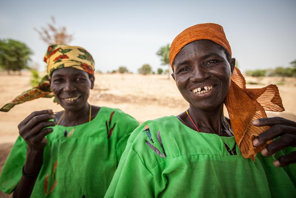 Two Nigerien women with facial scarifications wearing bright green shirts.