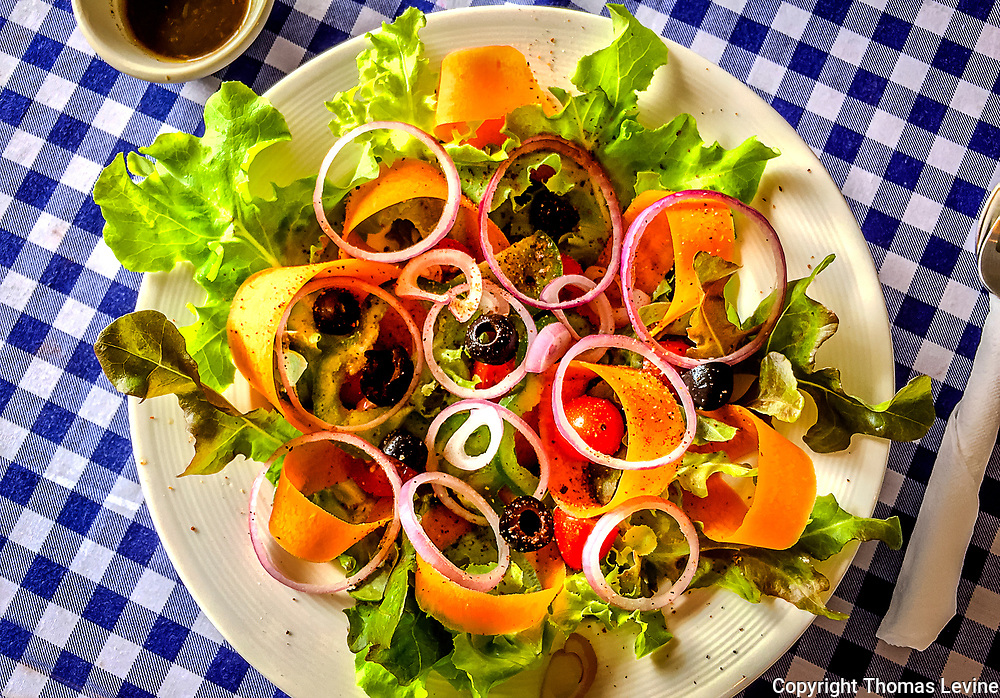 Assorted vegetables in a lettuce salad, checkered table cloth. (iPhone)