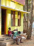 Young men readng the mornings papers near Trivandrum (Thiruvananthapuram), Kerala, India