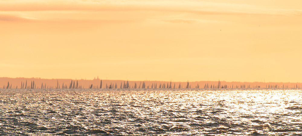 The world's largest and most famous yachting race, the 'JP Morgan Asset Management Round the Island Race, took place on the 1st June 2013, starting in Cowes, Isle of Wight, England. This panorama catches the main fleet as it approaches Yarmouth in the West Wight.