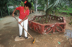 Woman sweeping up on the Rotonda de Cojimar organic allotment garden or Organoponico in Havana; Cuba,