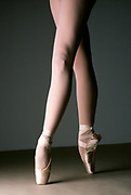 Ballerina's legs standing on point in pointe shoes, side lit in front of a gray background